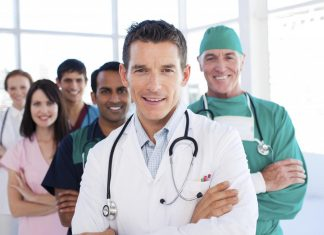 Atractive doctor standing with his colleagues